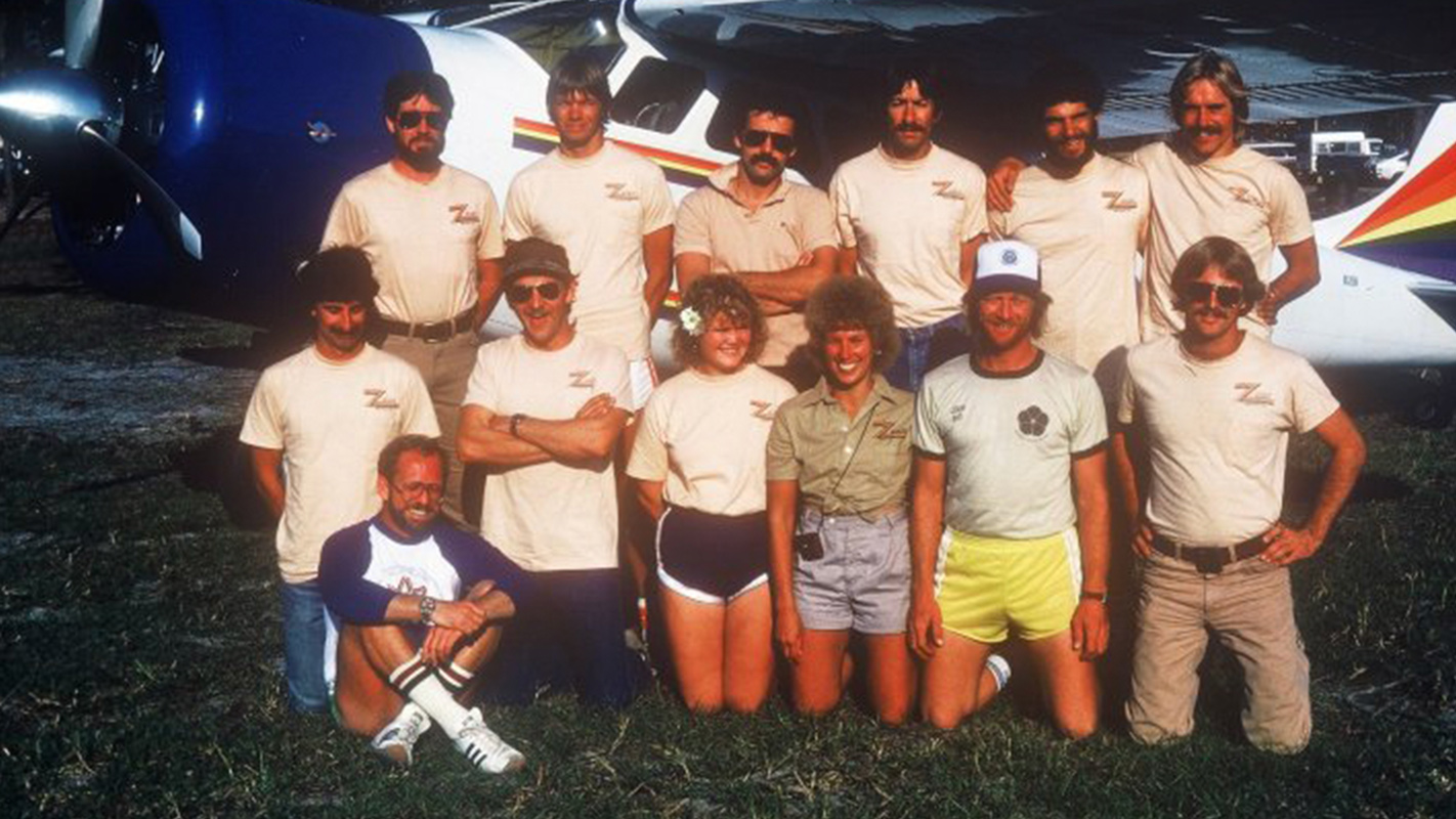 1970 Skydive City employees posing by airplane.