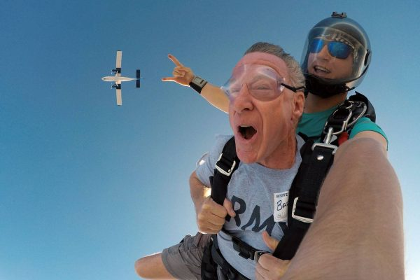 Male tandem skydiver enjoying freefall with Skydive City airplane above him.