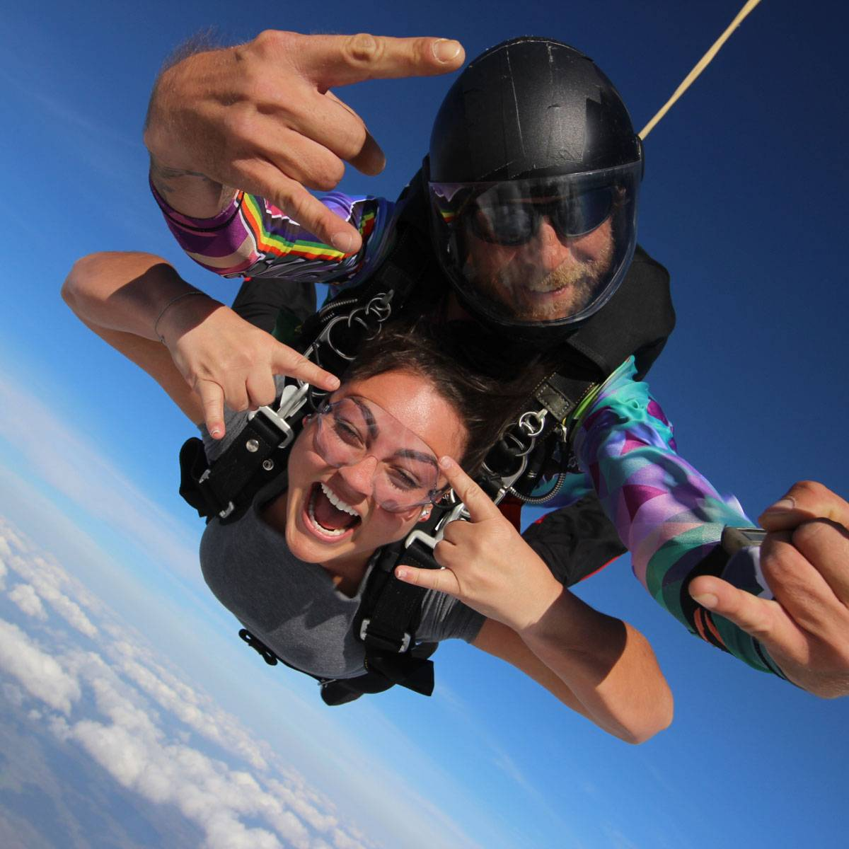 Female tandem skydiver and instructor giving rock on hand signs during free fall at Skydive City.