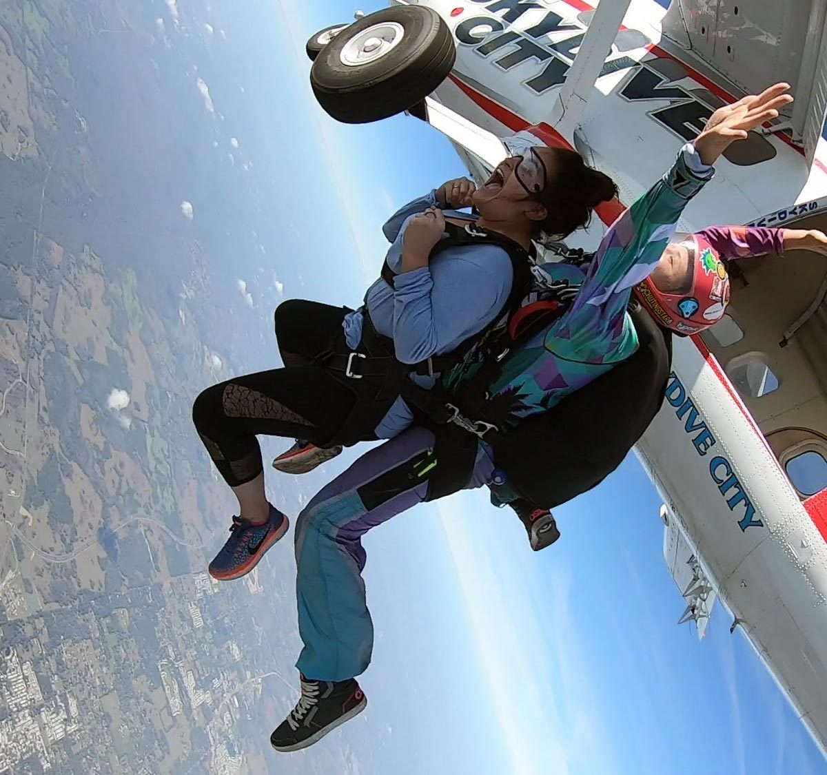 Women tandem jumper exiting Skydive City aircraft into freefall