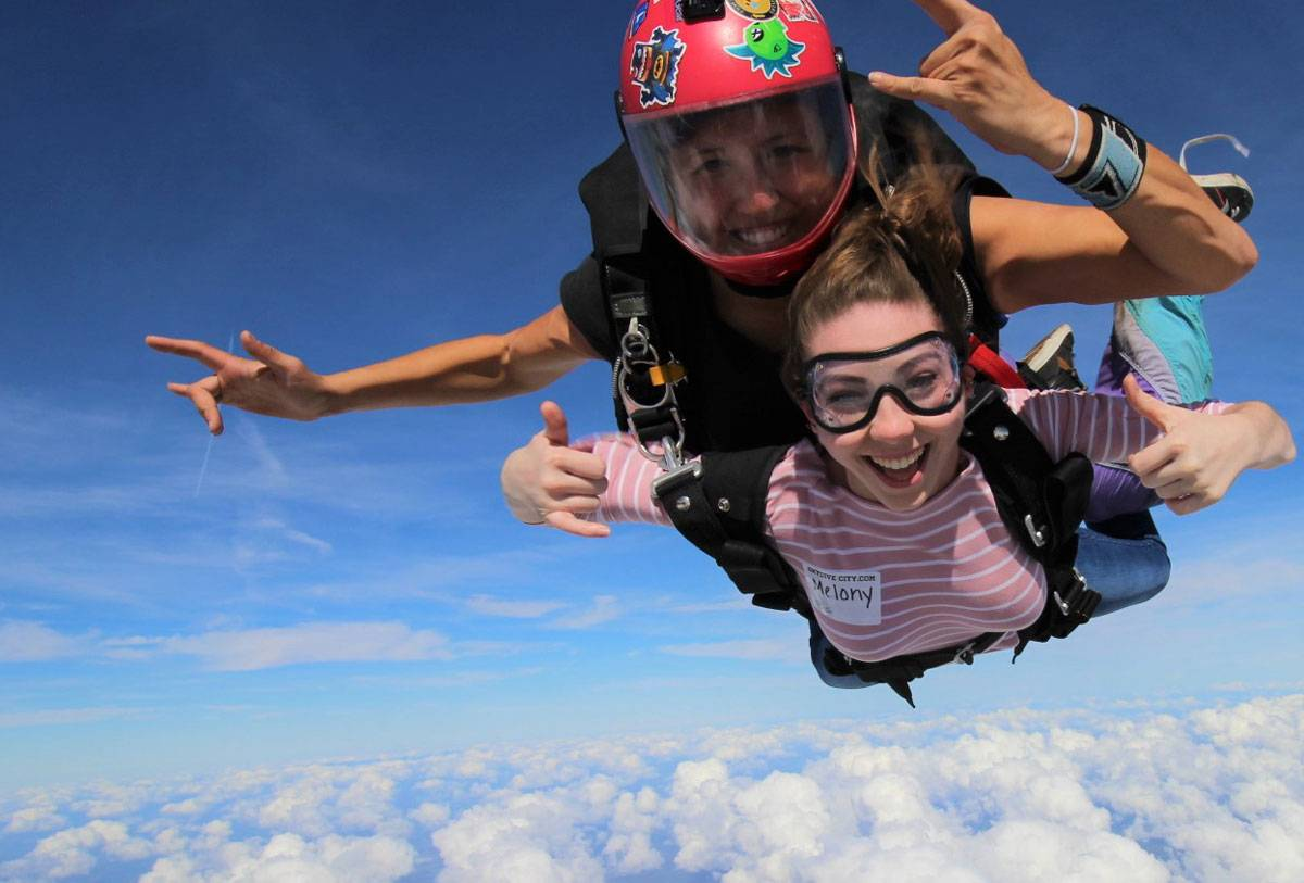 Female tandem skydiver wearing pink and white shirt giving thumbs up while in freefall.