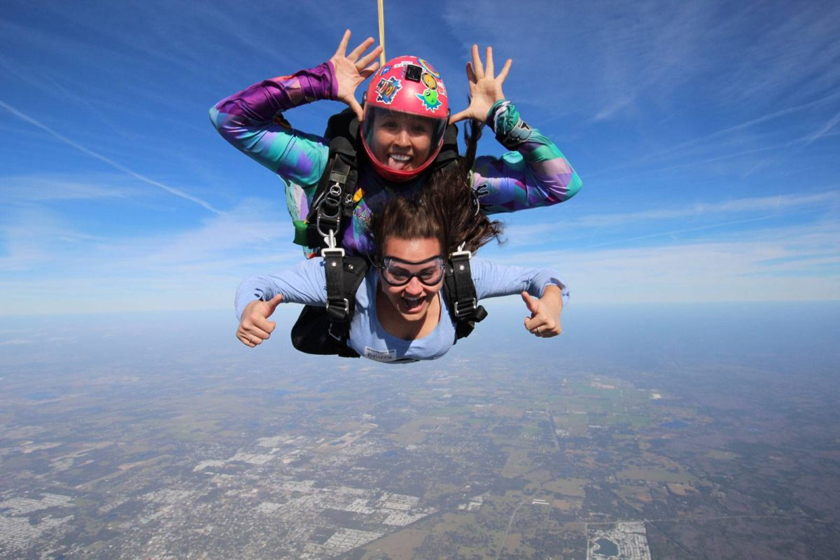 Female tandem jumper gives thumps up during freefall with Skydive City tandem instructor.