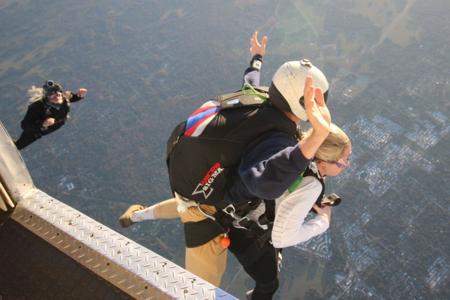 Women tandem jumper exiting Skydive City aircraft with instructor.