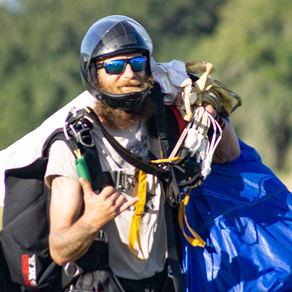 Dereck Dittman walking with skydiving canopy.