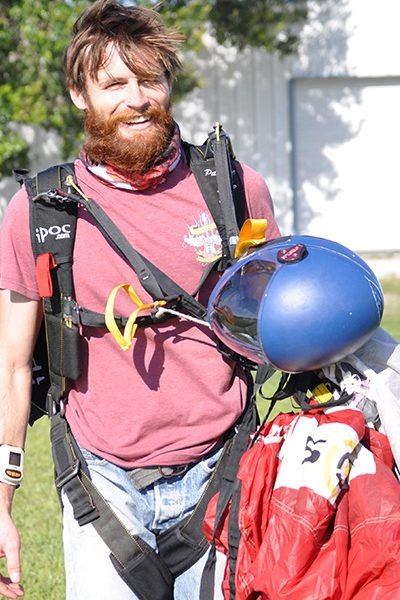 Dylan Bell holding canopy and skydiving helmet.