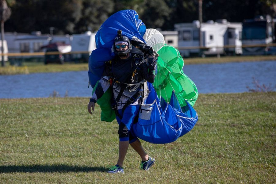 Experienced skydiver holding canopy while walking on grass at Skydive City