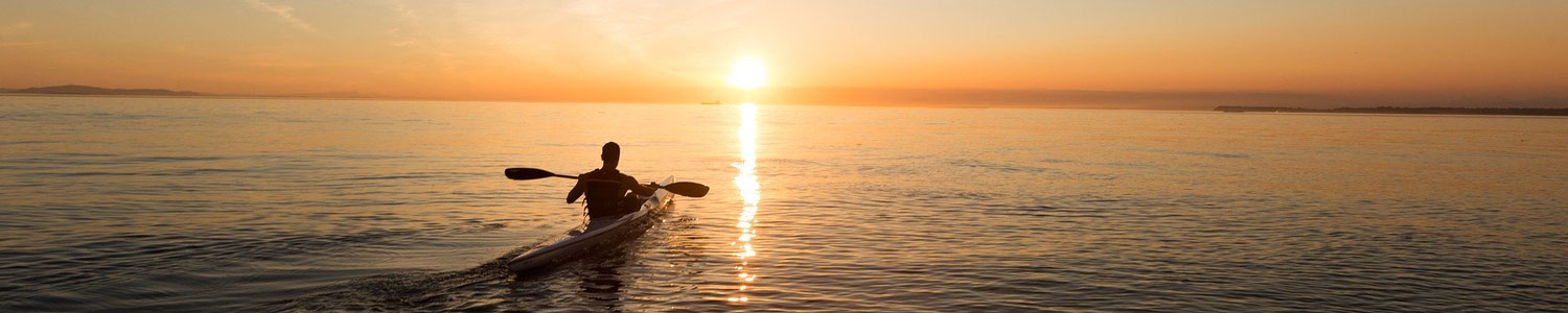 Man in kayak with sun setting in the distance.