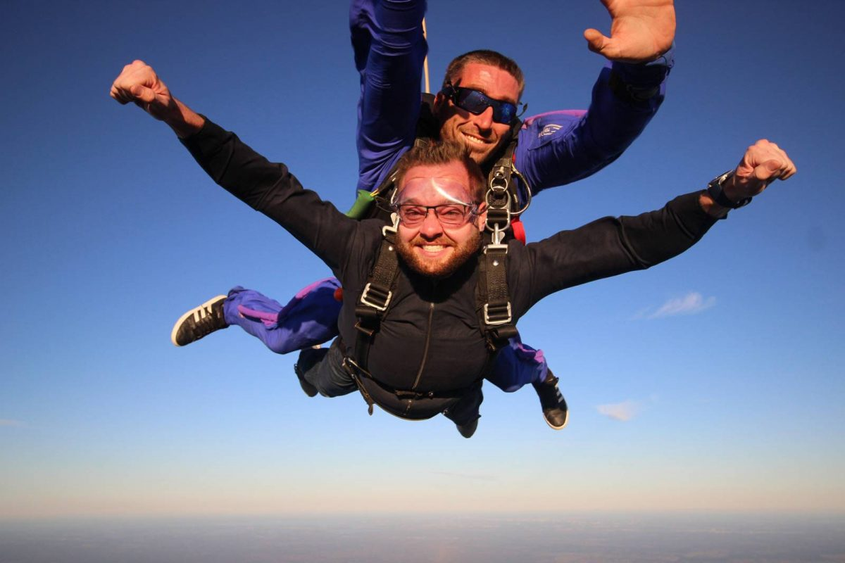 Male tandem jumper with arms out while in freefall with Skydive City tandem instructor.