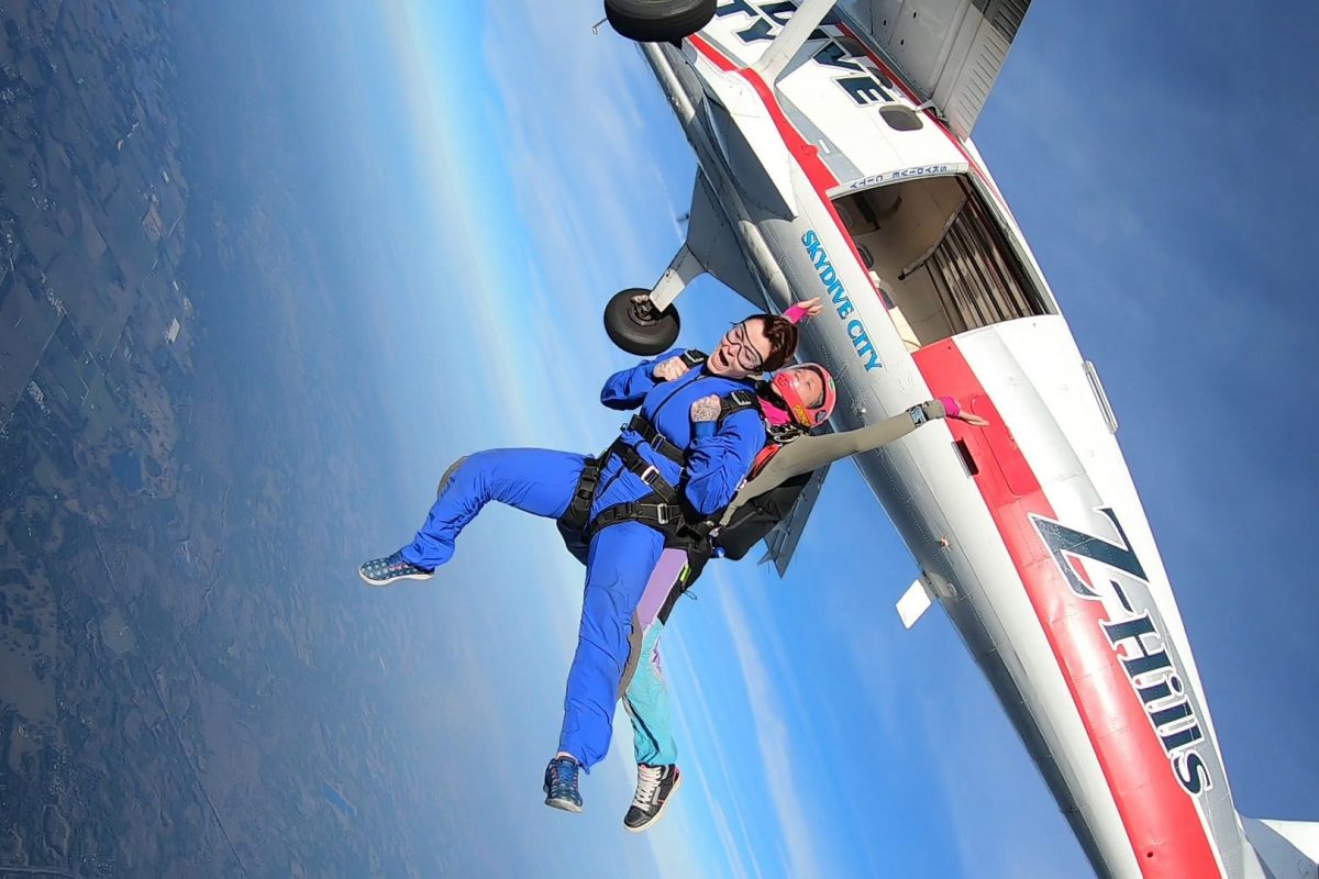 Female tandem skydiver jumping out of Skydive City airplane