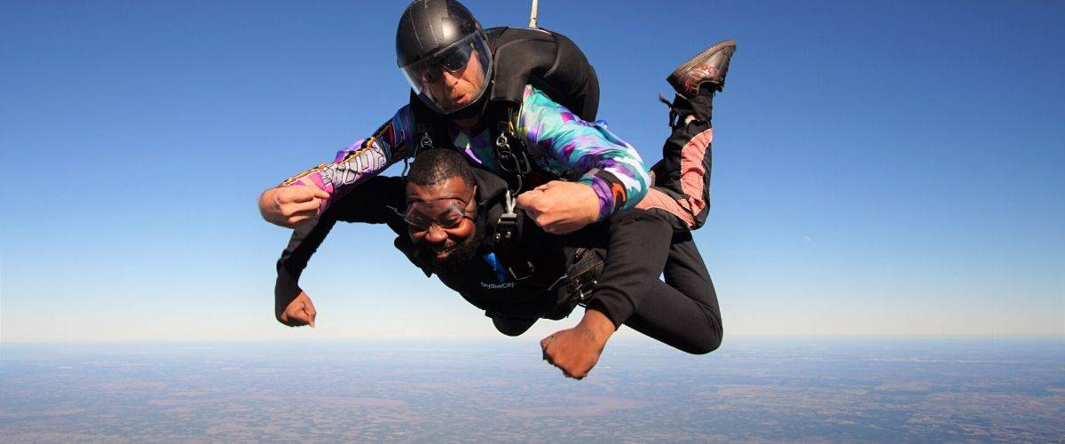 Male tandem skydiver happy to be in freefall with Skydive City tandem instructor