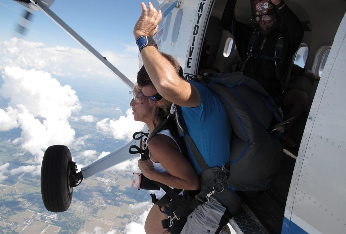 Women leaping out of airplane with tandem coach at Skydive City in Florida