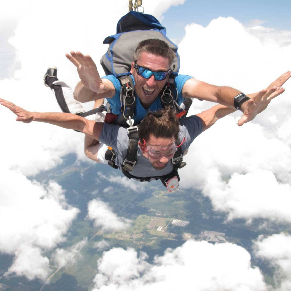 Male tandem instructor and student putting arms out during free fall.