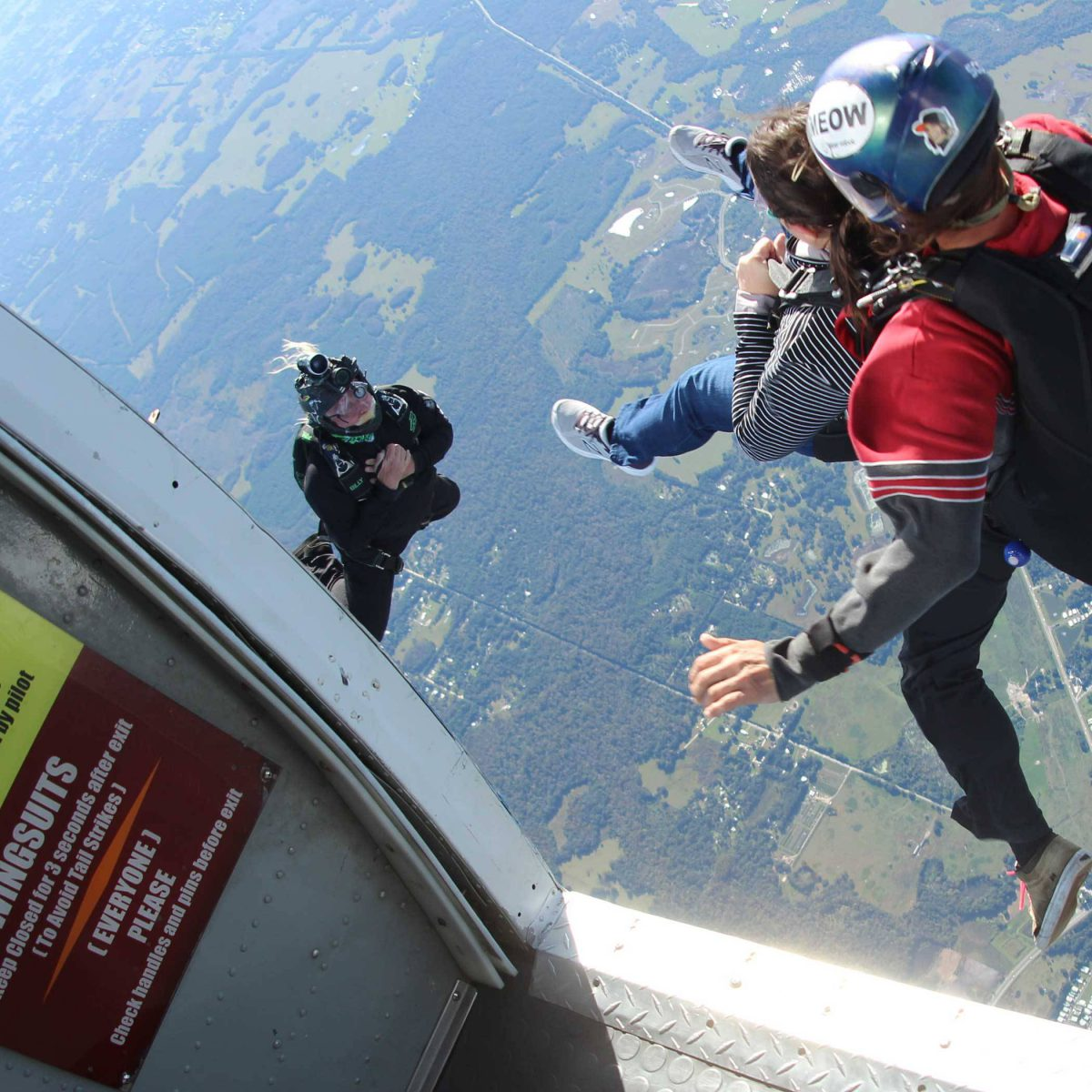 Female skydiver and instructor leaping from Skydive City Z-Hills airplane.