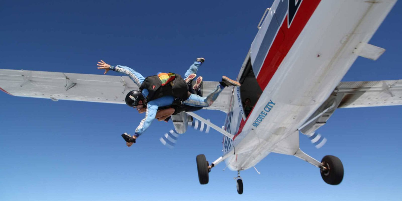 Female skydiver exiting Skydive City airplane with tandem instructor.