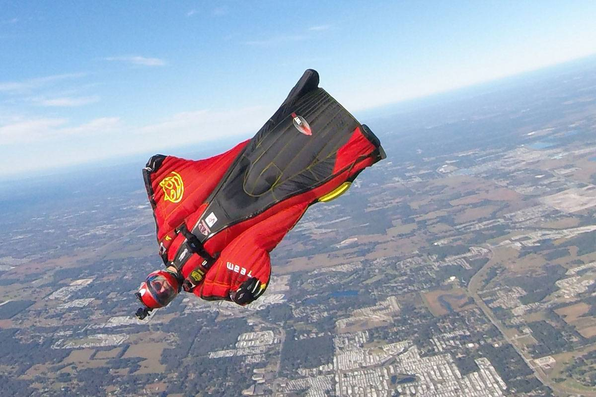 Travis Mickle wearing a red and black wingsuit
